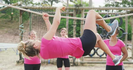 konkurenti : Side view of a happy multi-ethnic group of female friends enjoying exercising at boot camp together, one Caucasian woman hanging upside down, moving along a rope on a climbing frame and the others watching and motivating her in slow motion