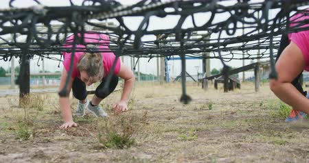 ползком : Low angle front view of two happy Caucasian women wearing pink t shirts enjoying exercising at boot camp together, crawling under a net, in slow motion