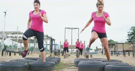 для взрослых : Front view of two happy Caucasian women wearing pink t shirts enjoying exercising at boot camp together, stepping through tyres, while other women wait for their turn in the background, in slow motion
