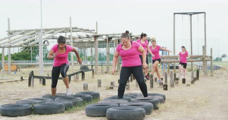 vyvažování : Side view of a happy multi-ethnic group of women wearing pink t shirts enjoying exercising at boot camp together, running through tyres and balancing on wooden posts, in slow motion