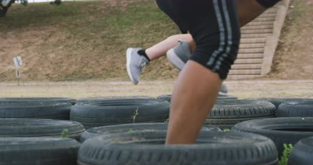 four legs : Side view low section of a multi-ethnic group of women wearing pink t shirts enjoying exercising at boot camp together, running through tyres in slow motion Stock Footage