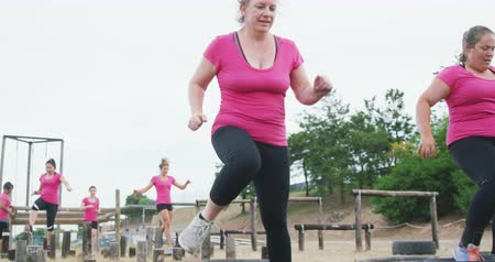 baixo : Low angle side view of two Cacuasian women wearing pink t shirts enjoying exercising at boot camp together, running through tyres, with other women competing in the background, in slow motion Vídeos