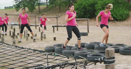 stepping : Side view of two happy Caucasian women wearing pink t shirts enjoying exercising at boot camp together, stepping through tyres, while other women wait for their turn in the background, in slow motion