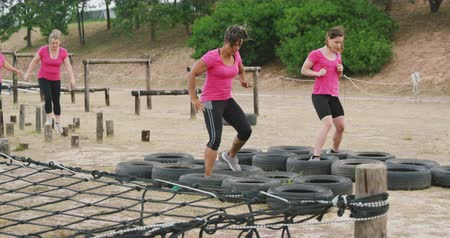 vyvažování : Side view of a happy Caucasian and mixed race woman wearing pink t shirts enjoying exercising at boot camp together, stepping through tyres, while other women balance on wooden posts in the background, in slow motion Dostupné videozáznamy
