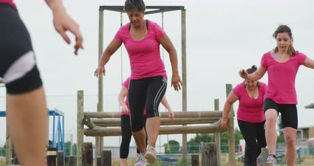 vyvažování : Front view of a happy multi-ethnic group of female friends wearing pink t shirts enjoying exercising at boot camp together, walking balancing on wooden posts, in slow motion