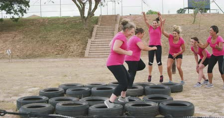 torcendo : Side view of a happy multi-ethnic group of female friends enjoying exercising at boot camp together, two of them running through tyres, the others motivating them and cheering, in slow motion Vídeos