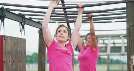 ハング : Front view of a Caucasian and a mixed race woman wearing pink t shirts enjoying exercising at boot camp, climbing on monkey bars, with other women waiting their turn in the background, in slow motion