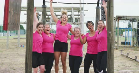 braços levantados : Front view of a happy multi-ethnic group of female friends wearing pink t shirts enjoying exercising at boot camp together, embracing, jumping and cheering, looking to camera and smiling with raised arms after training, in slow motion