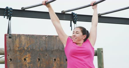 ハング : Side view close up of a Caucasian woman wearing a pink t shirt enjoying exercising at boot camp, climbing on monkey bars, in slow motion 動画素材