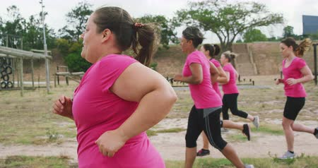 deneme : Side view of a happy multi-ethnic group of women wearing pink t shirts enjoying exercising at boot camp together, training and running in slow motion