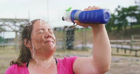 cooling : Side view close up of an exhausted Caucasian woman wearing a pink t shirt at boot camp, pouring water from a bottle on her face and refreshing herself after training, in slow motion