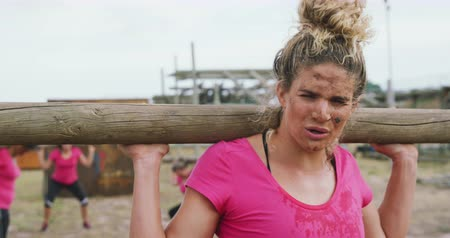 provést : Front view close up of an exhausted Caucasian woman wearing a pink t shirt standing at boot camp, holding a wooden post on her shoulders and looking at camera, with other women holding posts and working out in the background, in slow motion