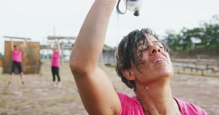 cooling : Front view close up of an exhausted mixed race woman wearing a pink t shirt at boot camp, pouring water from a bottle on her face and refreshing herself after training, with other women working out on the background, in slow motion Stock Footage