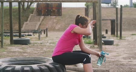 cooling : Side view of an exhausted Caucasian woman wearing a pink t shirt sitting on a tyre at boot camp, refreshing with water after training, in slow motion Stock Footage