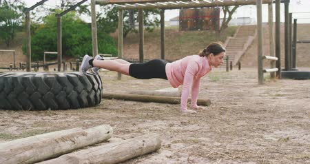 deneme : Side view of a Caucasian woman exercising at boot camp, doing push ups with her feet up on a tyre, in slow motion