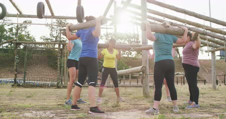 provést : Side view of a happy multi-ethnic group of female friends enjoying exercising at boot camp together, standing in a circle doing squats with wooden poles on their shoulders, in slow motion