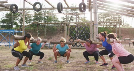 проведение : Front view of a happy multi-ethnic group of female friends enjoying exercising at boot camp together, standing in a circle doing squats with wooden poles on their shoulders, in slow motion