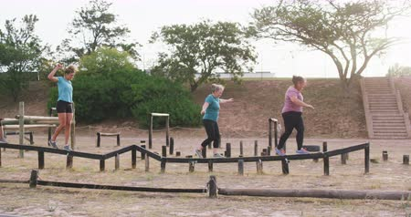 vyvažování : Side view of three happy Caucasian women enjoying exercising at boot camp together, balancing and walking along a wooden beam in a row, in slow motion