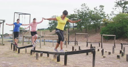deneme : Side view of a happy multi-ethnic group of women enjoying exercising at boot camp together, balancing and walking along a wooden beam in slow motion Stok Video