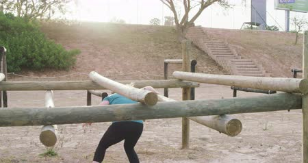 deneme : Side view of two Caucasian women enjoying exercising at boot camp, climbing over and under wooden posts on a climbing frame, backlit by sunlight, in slow motion