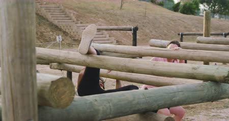 competidores : Side view of a happy multi-ethnic group of female friends enjoying exercising at boot camp together, climbing over and under wooden posts on a climbing frame, in slow motion Archivo de Video