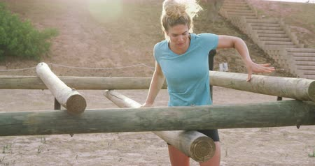 deneme : Side view of a Caucasian woman enjoying exercising at boot camp, climbing over and under wooden posts on a climbing frame, backlit by sunlight, in slow motion Stok Video