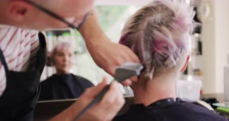 dyeing : Alternative cool hair salon. Rear view close up of a Caucasian male hairdresser working in a hair salon, holding brush, colouring hair of a Caucasian female client, reflecting in a mirror, in slow motion Stock Footage