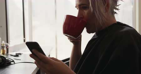 individualidade : Alternative cool hair salon. Side view of a Caucasian female client in a hair salon sitting, drinking a cup of coffee, using smartphone, in slow motion Stock Footage