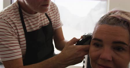 egyéniség : Alternative cool hair salon. Front view close up of a Caucasian male hairdresser working in a hair salon, trimming hair of a Caucasian female in slow motion