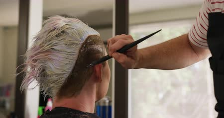 краситель : Alternative cool hair salon. Side view close up of a Caucasian male hairdresser working in a hair salon, holding brush, colouring hair of a Caucasian female client in slow motion