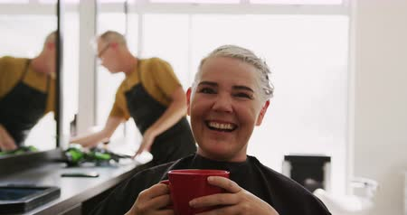 individualidade : Alternative cool hair salon. Portrait of a Caucasian female client in a hair salon sitting, drinking a cup of coffee, smiling, with a Caucasian male hairdresser in the background, in slow motion