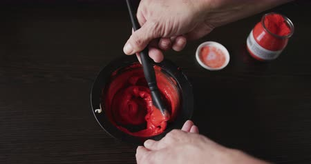individualidade : Alternative cool hair salon. Close up detail of a Caucasian male hairdresser working in a hair salon, mixing a red dye in a dish, in slow motion