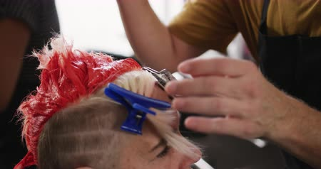 dyeing : Alternative cool hair salon. Side view close up of a Caucasian male hairdresser working in a hair salon, untying hair of a Caucasian female from hair clips in slow motion