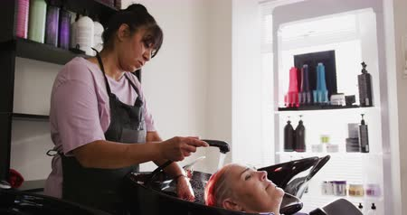 パーラー : Alternative cool hair salon. Side view of a Caucasian female client in a hair salon, having her red hair washed by a mixed race female hairdresser working in a hair salon, in slow motion