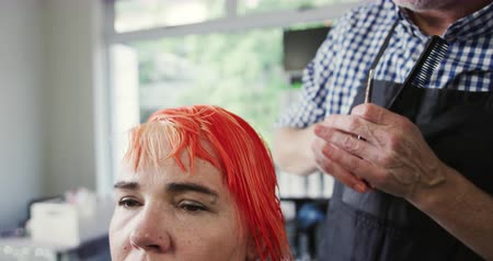 individualidade : Alternative cool hair salon. Front view of a Caucasian male hairdresser working in a hair salon, combing and stroking red hair of a Caucasian female client, in slow motion Stock Footage