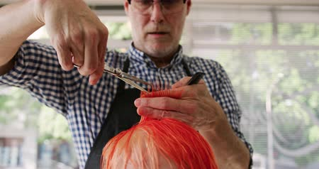 grzebień : Alternative cool hair salon. Front view of a focused Caucasian male hairdresser working in a hair salon, holding a comb and cutting red hair of a Caucasian female client, in slow motion