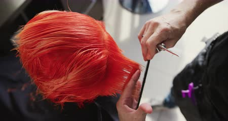 grzebień : Alternative cool hair salon. High angle view close up of a Caucasian male hairdresser working in a hair salon, combing and cutting red hair of a Caucasian female client, in slow motion Wideo
