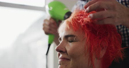 сушка : Alternative cool hair salon. Side view close up of a Caucasian male hairdresser working in a hair salon, holding a hair dryer, drying and stroking red hair of a happy Caucasian female client, in slow motion