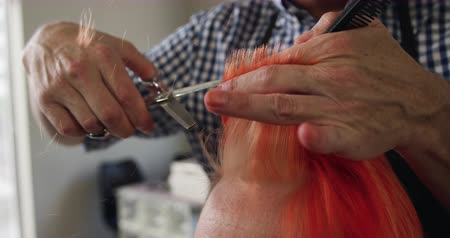 grzebień : Alternative cool hair salon. Front view close up of a Caucasian male hairdresser working in a hair salon, holding a comb, cutting, combing and stroking red hair of a Caucasian female client, in slow motion