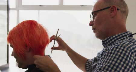 grzebień : Alternative cool hair salon. Side view close up of a Caucasian male hairdresser working in a hair salon, holding a comb, cutting and combing red hair of a Caucasian female client, in slow motion Wideo
