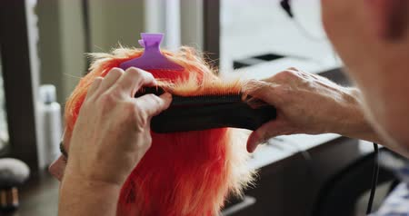 individualidade : Alternative cool hair salon. Rear view close up of a Caucasian male hairdresser working in a hair salon, modeling and straightening with a hair straightener red hair of a Caucasian female client using smartphone, in slow motion