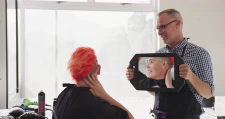 odrážející : Alternative cool hair salon. Side view of a happy Caucasian male hairdresser working in a hair salon, holding a mirror for a Caucasian female client, reflecting in it, admiring her new haircut, in slow motion Dostupné videozáznamy
