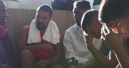 fotbal : Front view of a disappointed multi-ethnic group of male football players wearing sportswear, sitting in changing room, resting, in slow motion