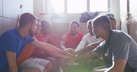 empilhamento : Front view of a happy multi-ethnic group of male football players wearing sportswear, sitting in changing room, interacting and motivating each other, hand stacking, backlit by sunlight, in slow motion Vídeos