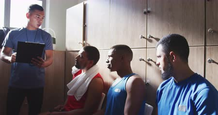 fotbal : Front view of a multi-ethnic group of male football players wearing sportswear, sitting in changing room, their mixed race coach holding a clipboard and motivating, in slow motion