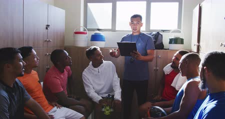fotbal : Front view of a happy multi-ethnic group of male football players wearing sportswear, sitting in changing room, their mixed race male coach holding a clipboard and motivating, in slow motion