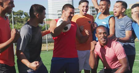torcendo : Front view of a multi-ethnic group of male football players wearing sportswear, training at a sports field in the sun, cheering and celebrating, in slow motion