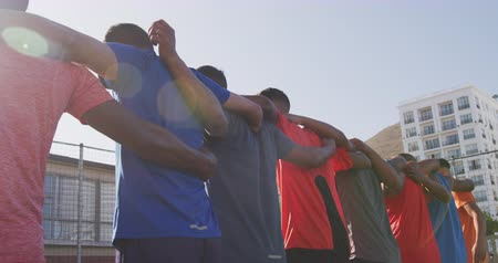 fotbal : Low angle rear view of a multi-ethnic group of male football players in casual sportswear, standing in a row on a playing field on a sunny day, embracing, holding a football, in slow motion