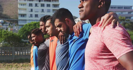 fotbal : Side view of a multi-ethnic group of male football players in casual sportswear, standing in a row on a playing field on a sunny day, embracing, holding a football, in slow motion