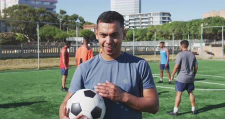kop : Portrait of a mixed race male football player wearing sportswear, looking at camera, holding a football, his teammates training at a sports field in the sun, in slow motion Dostupné videozáznamy